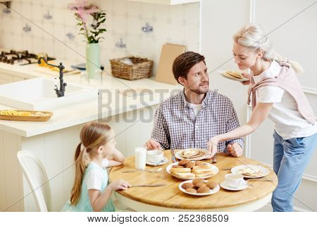 Smiling beautiful wife in casual clothing giving pancakes to family and putting plates with dessert on table, happy father and daughter waiting for their breakfast in kitchen