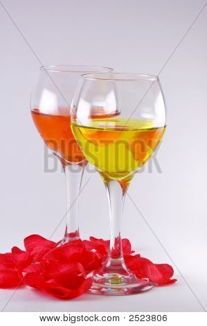 Two Wine Glasses With Wine And Rose Pedals