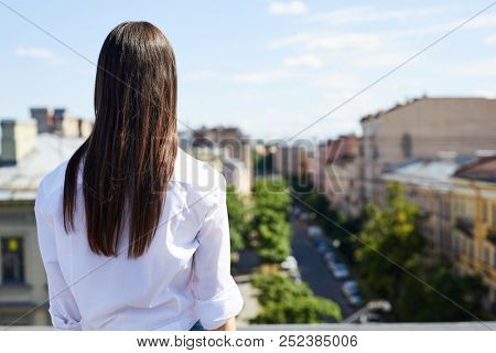 Rear view of dreamy brunette girl in white shirt standing on roof and looking at city while thinking about future