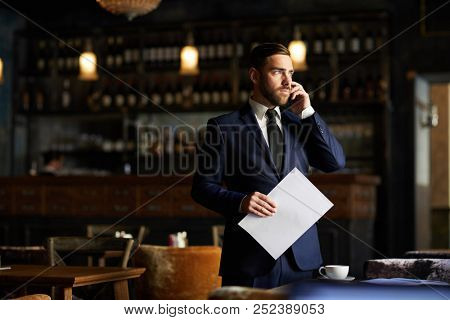 Serious confident handsome male entrepreneur in formal suit standing at table and holding contract while solving problems on phone in own restaurant