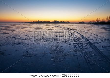 Trails On The Surface Of Frozen Lake. Winter Landscape With Trails On Frozen Lake And Sunset Fiery S