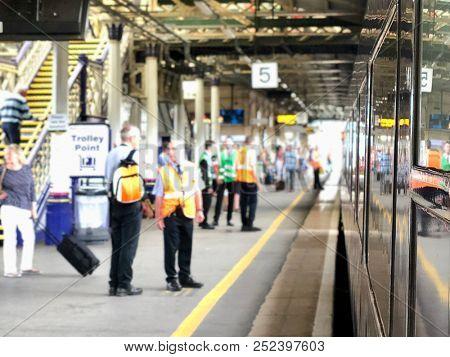 EXETER, UK - JULY 16, 2018: People on platform 5 as a train departs Exeter St. Davids train station in Exeter, Devon, UK.