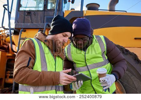 Waist Up Portrait Of Two Workers, One African-american, Drinking Coffee And Using Digital Tablet Sta