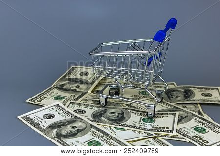 Empty Shopping Basket On A Pile Of Dollars.