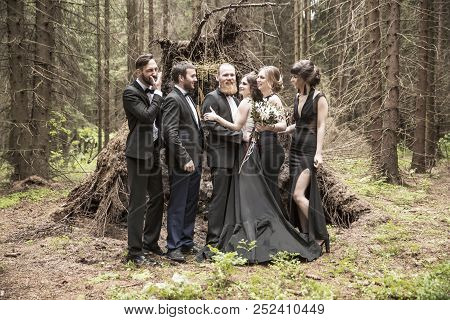 Portrait Of The Couple And The Witnesses In The Background Of A Hut In The Woods