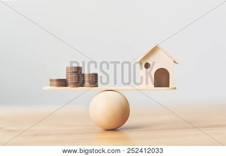 Wooden Home And Money Coins Stack On Wood Scale. Property Investment And House Mortgage Financial Re
