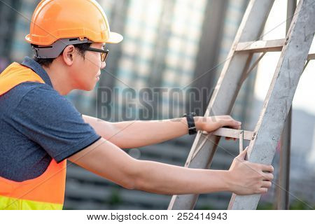 Young Asian Maintenance Worker Man With Orange Safety Helmet And Vest Carrying Aluminium Step Ladder