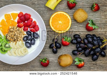 Plate Of Natural White Yogurt With Muesli, Orange, Banana, Kiwi, Strawberries And Grapes Fruits On W