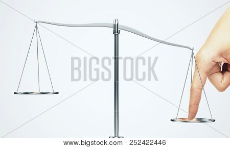 Tip The Scales Of Justice Concept. Finger Illegaly Influencing The Legal System For An Unfair Advant