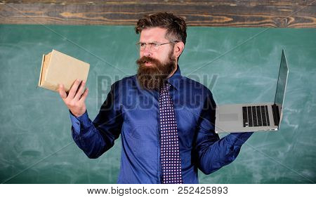 Teacher Bearded Hipster Holds Book And Laptop. Choose Right Teaching Method. Teacher Choosing Modern