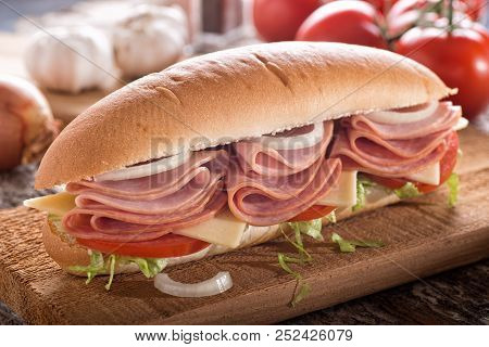 A Delicious Submarine Sandwich With Deli Meats, Lettuce, Tomato, Onion And Cheese On A Sub Bun.