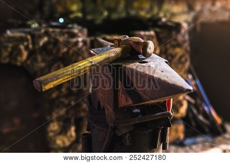 Dark smithy with blacksmith tools, hammer and anvil poster