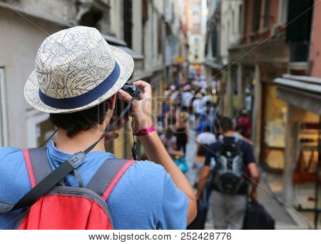 Young Photographer With Digital Camera And Big Hat Takes Many Photos In Venice In Italy