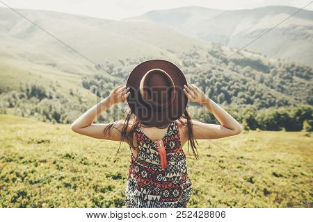 Travel And Wanderlust Concept. Traveler Hipster Girl Holding Hat, Looking At Sunny Mountains. Summer