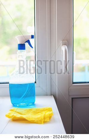 A Blue Window Cleaner, A Yellow Rag On A White Window Sill Against The Window. Carrying Out Home Ins