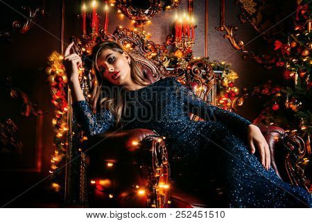 Magical Christmas night. Beautiful woman in evening dress celebrates Christmas in luxurious apartments decorated christmas lights.