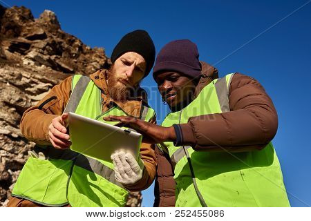Low Angle Portrait Of Two Industrial Workers Wearing Reflective Jackets, One Of Them African, Inspec