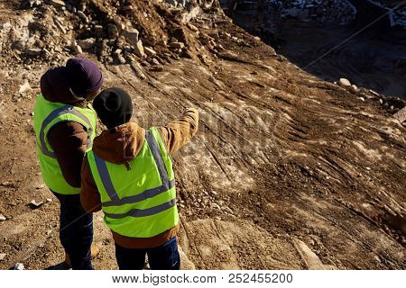 Back View Portrait Of Two Industrial Workers Wearing Reflective Jackets, One Of Them African, Standi