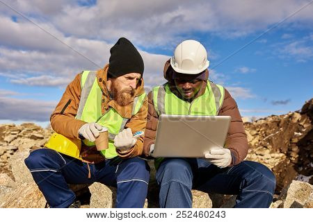 Portrait Of Two Industrial  Workers Wearing Reflective Jackets, One Of Them African, Using Laptop On