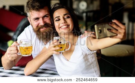 Couple In Love On Date Drinks Beer. Couple Cheerful Mood Drinking Beer In Pub. Man Bearded Hipster A