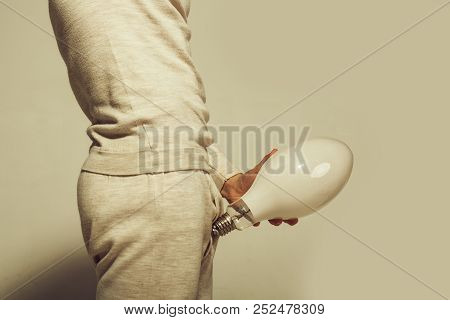 Man With Big Lamp Near Pants. Electricity