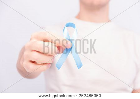 Oncological Disease Concept. Man In White T-shirt Holding Light Blue Ribbon As A Symbol Of Prostate