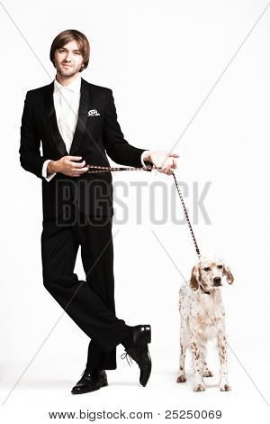 handsome  young  man in tuxedo and his dog, studio shot poster