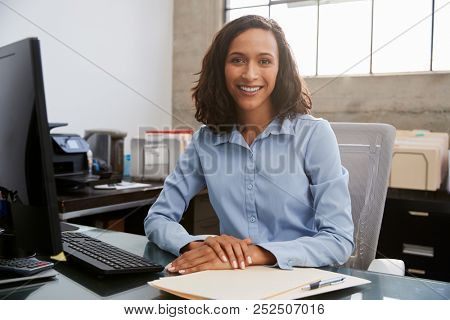 Young female professional sitting at desk in an office