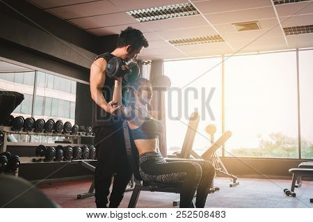 Personal Trainer Helping Woman Working Lift Heavy Dumbbells.