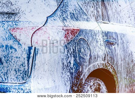 Blue Compact Suv Car With Sport And Modern Design Washing With Soap. Car Covered With White Foam. Ca