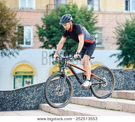 Handsome Man Bicyclist In Cycling Clothing And Protective Gear Riding Down Concrete Stairs In City U
