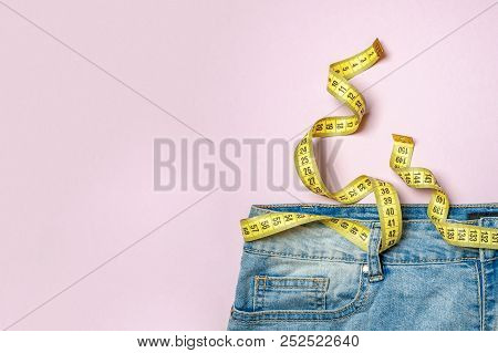 Jeans And Yellow Measuring Tape Instead Of Belt On Pink Background. Concept Of Weight Loss, Diet, De