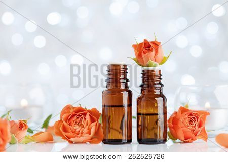 Rose Essential Oil Bottles On White Table With Bokeh Effect. Spa, Aromatherapy, Wellness, Beauty Bac