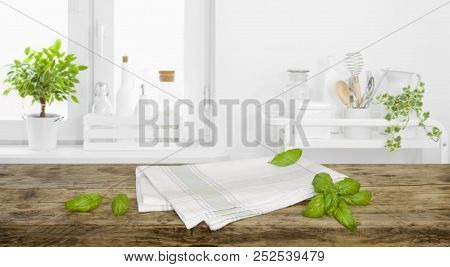 Brown Tabletop With Towel And Leaves On Defocused Kitchen Background