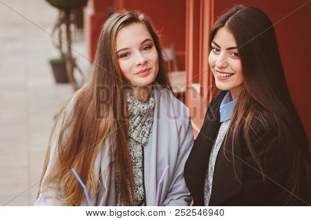 Two Happy Girl Friends Talking And Drinking Coffee In Autumn City In Cafe. Meeting Of Good Friends,