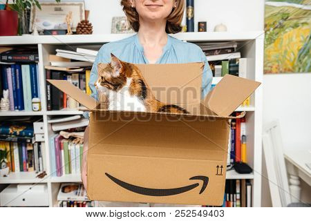 Paris, France - Jul 4, 2018: Woman Unboxing Cardboard With Cat Inside - New Delivery From Amazon E-s
