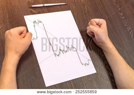 Man Sitting At Table. There Are Sheet Of Paper With A Trading Chart On The Table. Angry Gesture With