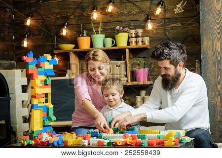 Construction Concept. Little Child With Mother And Father Play With Toy Construction Set. Family Bui