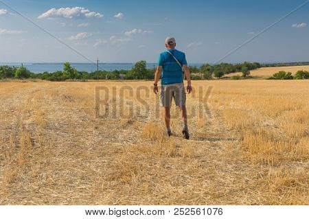 Mature Hiker Heading For Dnipro River Through Harvested Wheat Field In Ukraine