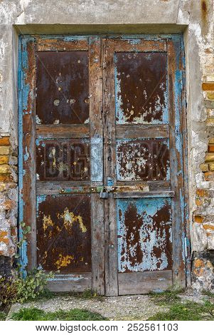 Old Architectural Details - Rusty Door In An Ancient Building Locked With Small Rusty Padlock