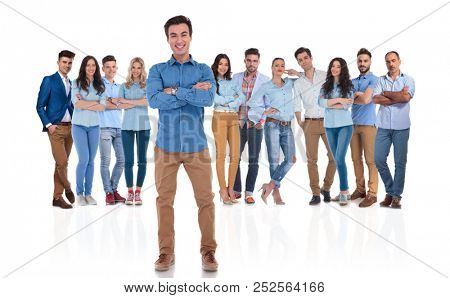 happy and confident team leader standing with arms crossed in front of his young casual group on white background, full body picture
