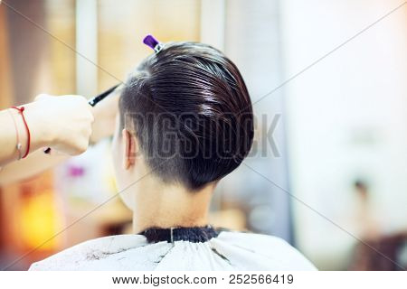 Beauty, hairstyle, treatment, hair care concept, young woman and hairdresser cutting hair at hairdressing salon. Hairdresser cuts beautiful girl's hair. Hairstylist serving client at barber shop