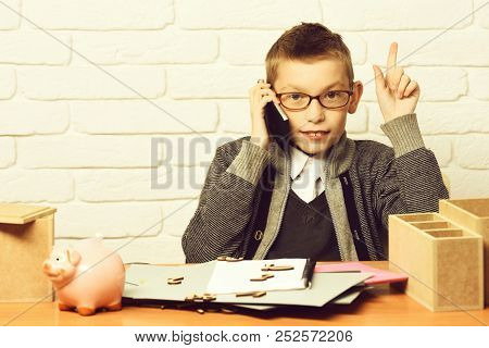 Piggy Pig Bank Holding And Speaking On Cell Phone On White Brick Wall Background, Copy Space. Young