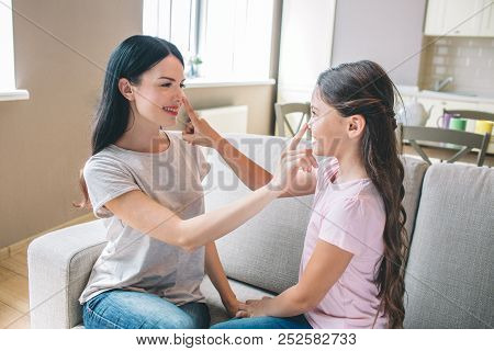 Beautiful Girls Are Sitting On Sofa And Looking At Each Other. They Are Touching Noses. Girls Are Sm