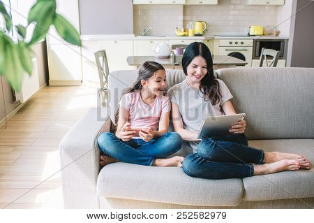 Nice Icture Of Woman And Girl Sitting Together On Sofa. Child Looks At Tablet Her Mom Has. Kid Holds