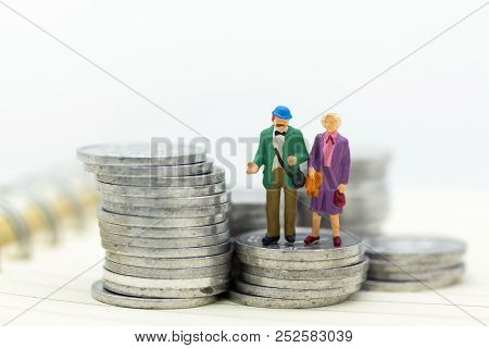 Miniature People, Adult Couple Figure Standing On Top Of Stack Coins . Image Use For Background Reti