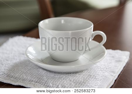 An Empty White Cup And A Saucer Stand On A Wooden Table