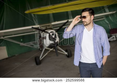Handsome Young Pilot Checking Airplane In The Hangar And Using Mobile Phone