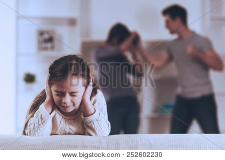 Sad Girl And Quarreling In Kitchen. Violence In Family Concept. Suffering Of Child. Conflicts Of Par