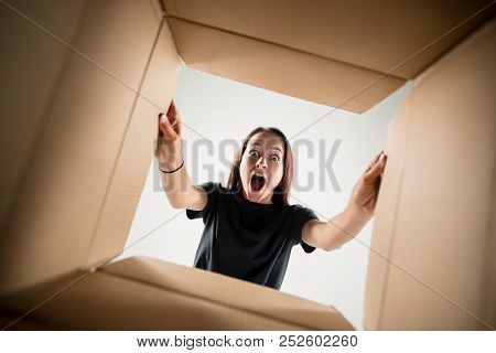 The Surprised Woman Unpacking, Opening Carton Box And Looking Inside. The Package, Delivery, Surpris